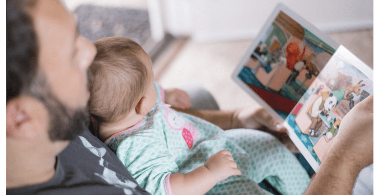 A dad reading to his infant. Vaccine safety matters. | Jennifer Margulis