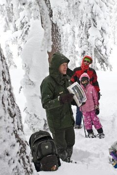 Ranger Dave Grimes holds up a photograph of lichen on a hemlock tree during the 1.5-hour interpretive snowshoe walk that he is leading. The author's husband, James, of Ashland, Oregon, and daughter Hesperus, in the background. Photo by Jennifer Margulis
