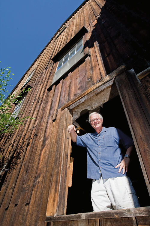 Bob Russell standing in the window of the Butte Creek Mill. Photo by Jamie Lusch, courtesy of Oregon Business Magazine.