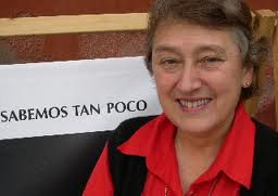 Lynn Margulis standing by a sign that reads, we know so little, in Spanish