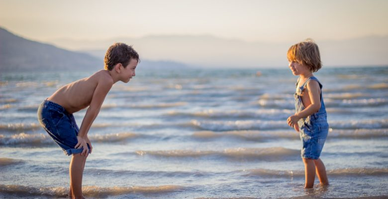 10 tips for traveling solo with kids. Photo of two children at the beach, courtesy of Limor Zellermayer, via Unsplash. | Jennifer Margulis