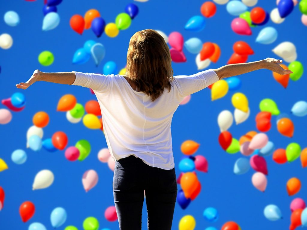 Say yes to happiness but what do you say to blog giveaways? Yay or nay? Photo of a woman glorying in balloons via Pixabay. | Jennifer Margulis