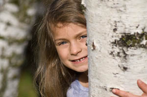 A first grader peeks out from a birch tree during a first grade photo shoot