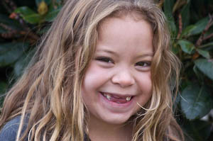 First grade photo shoot: girl smiling with messy blonde hair | Jennifer Margulis