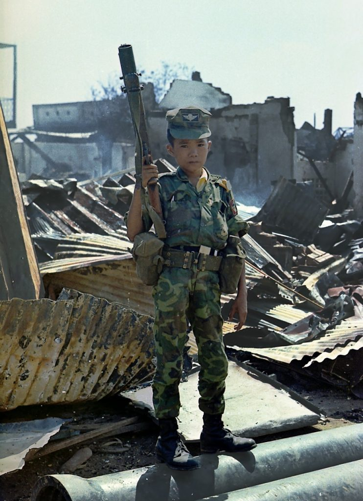 A child soldier stands at attention with a huge gun. Children and war is the subject of an anthology of stories edited by J. L. Powers. | Jennifer Margulis