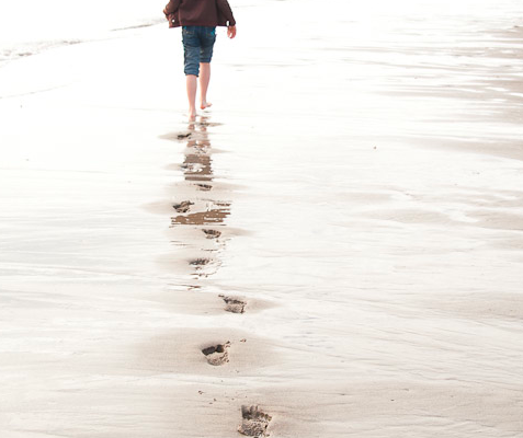 A young girl walking along the beach in the Taft District of Lincoln City, Oregon.