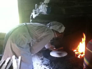Which is then cooked on an open hearth fire. In this photo a museum employee, dressed like a Norwegian baker of old, checks if it's time to flip the Norwegian flat bread