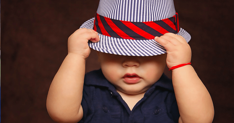 When your toddler is driving you crazy. Photo of a baby wearing a striped hat. Via Jennifer Margulis, Ph.D.