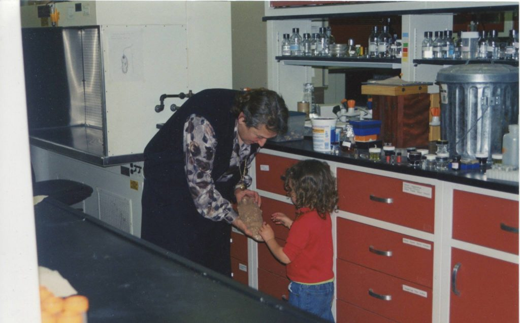 Evolutionary biologist Lynn Margulis, Ph.D., showing a fossil to her granddaughter at her laboratory at University of Massachusetts, Amherst. Photo credit: Jennifer Margulis