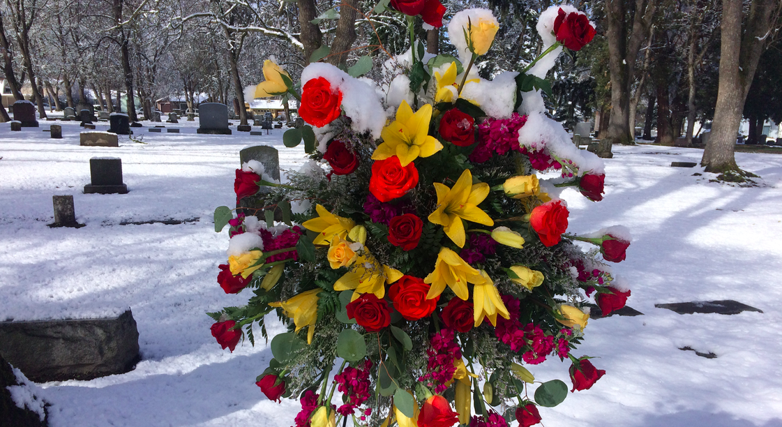 Do you want to be buried or cremated? Flowers at the cemetery in Ashland, Oregon on a snowy day. Photo by Jennifer Margulis