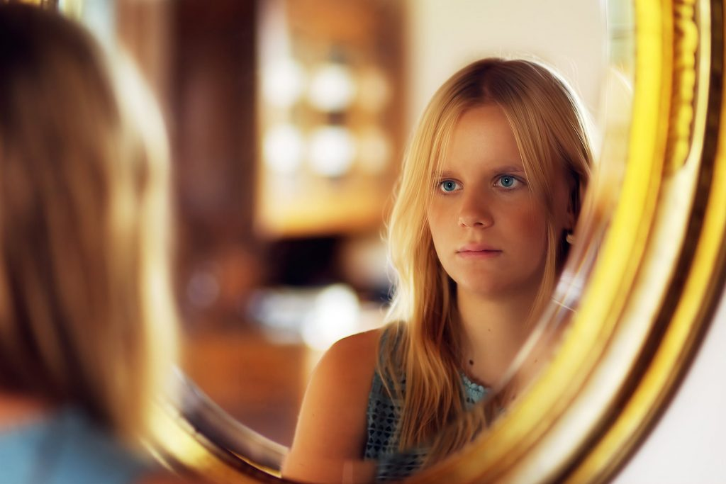 Are you being overly critical of your kids? Or of yourself? | photo of a young woman looking in the mirror, courtesy of Johannes Plenio.