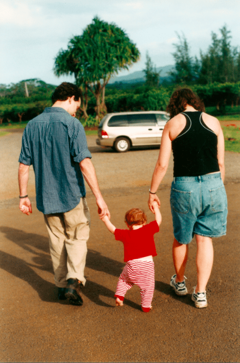 A young couple walks with their toddler, wearing striped pants and a red shirt, between them. Marriage is hard. How can we make it easier?
