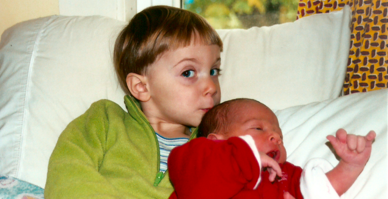 Big sister kisses her newborn baby brother on the head. He was born perfect. No need to cut off part of his penis. Via JenniferMargulis.net