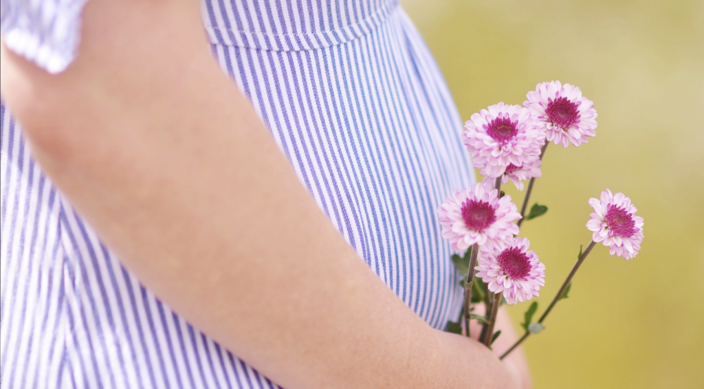 You feel exhausted. And nauseous. But does that mean you're pregnant? Here are five sure signs of pregnancy. Photo of a pregnant belly in a blue dress holding pink flowers, courtesy of Ashton Mullins