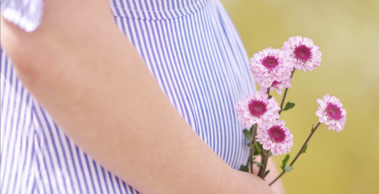 You feel exhausted. And nauseous. But does that mean you're pregnant? Photo of a pregnant belly in a blue dress holding pink flowers, courtesy of Ashton Mullins