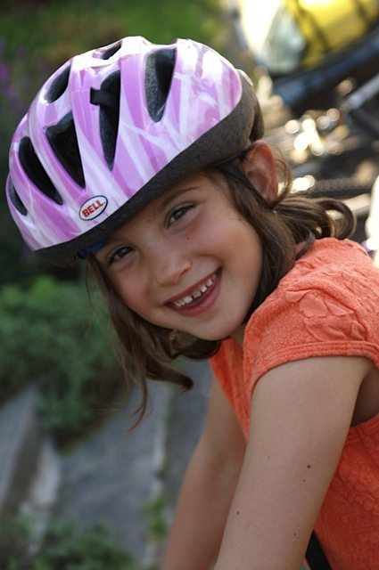 A little girl wearing a pink bike helmet. Bike safety matters. Here are the bike tips you need to keep your family safe.