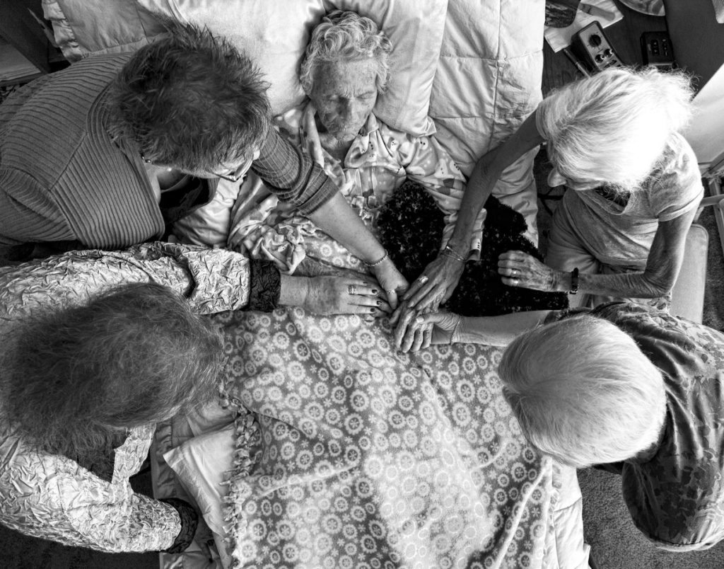 Dying comfortably surrounded by loved ones is a death with dignity. But how do we make sure that's what happens? Photo of a dying woman with her friends courtesy of Mary Landberg.