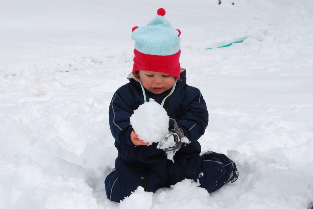 A toddler plays in the snow. When hurry becomes a habit, everyone is unhappy. Stop rushing. Let them play. Photo by Lora Horvath