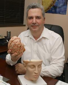 M.D./Ph.D. researcher Manuel Casanova has concerns about ultrasound safety when used during pregnancy. Photo of him holding a human brain. Via Jennifer Margulis.