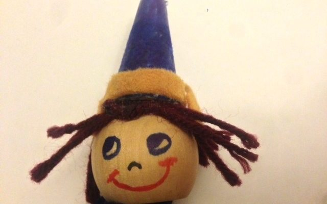 An elf pop-up puppet wearing a blue hat with a khaki rim and brown yarn for hair | Photo credit Jennifer Margulis, Ph.D.