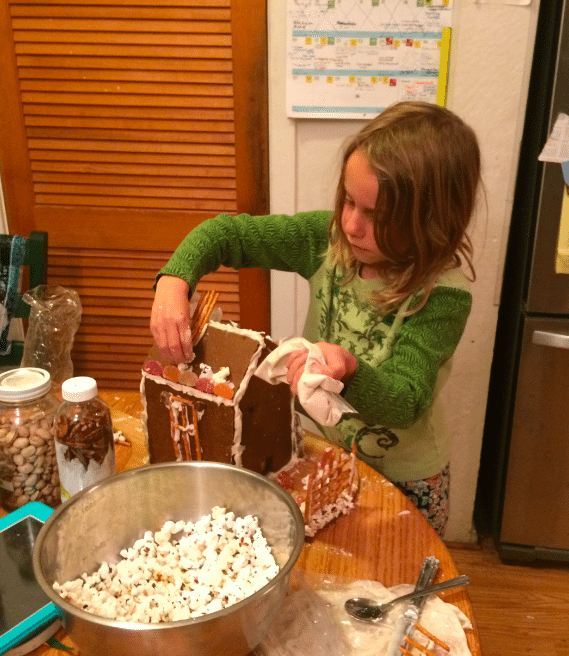 Using royal icing as glue to decorate a whole grain gingerbread house. Photo credit: Jennifer Margulis.