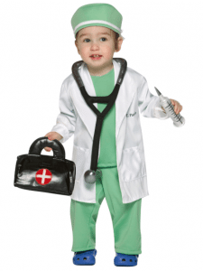 A toddler dressed as a doctor holding a medical bag and a vaccine. Many doctors in America are concerned we are giving too many vaccines too soon.