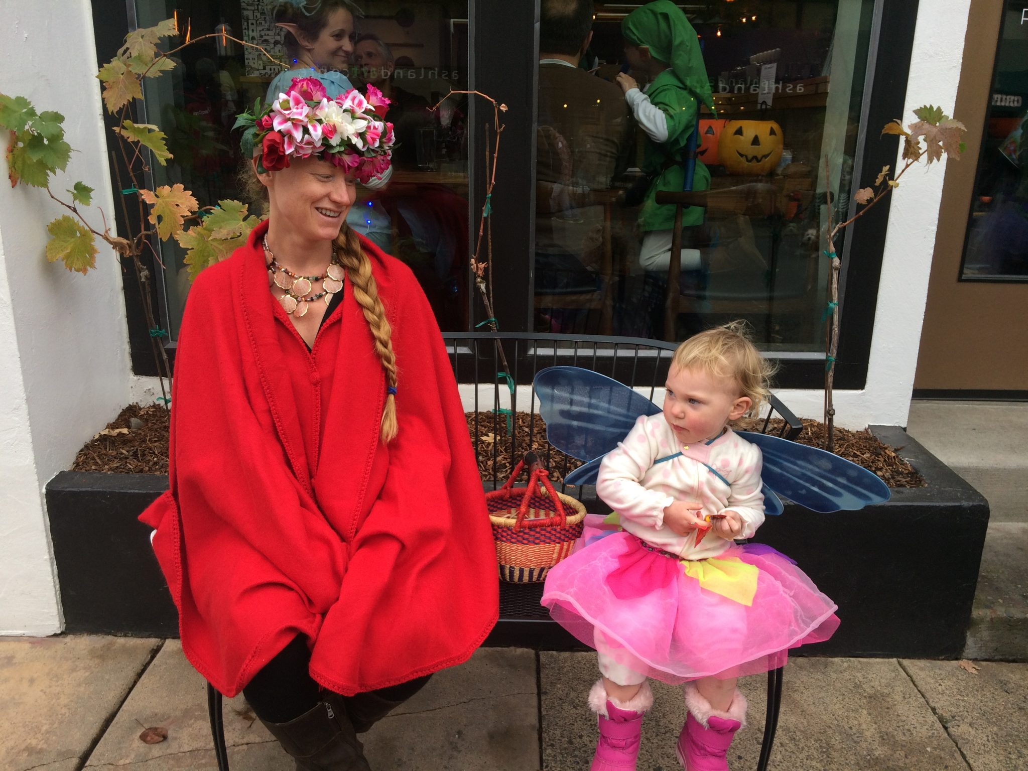 A butterfly and some flowers rest on a bench and eat Skittles outside Pie and Vine during the Halloween parade in Ashland, Oregon