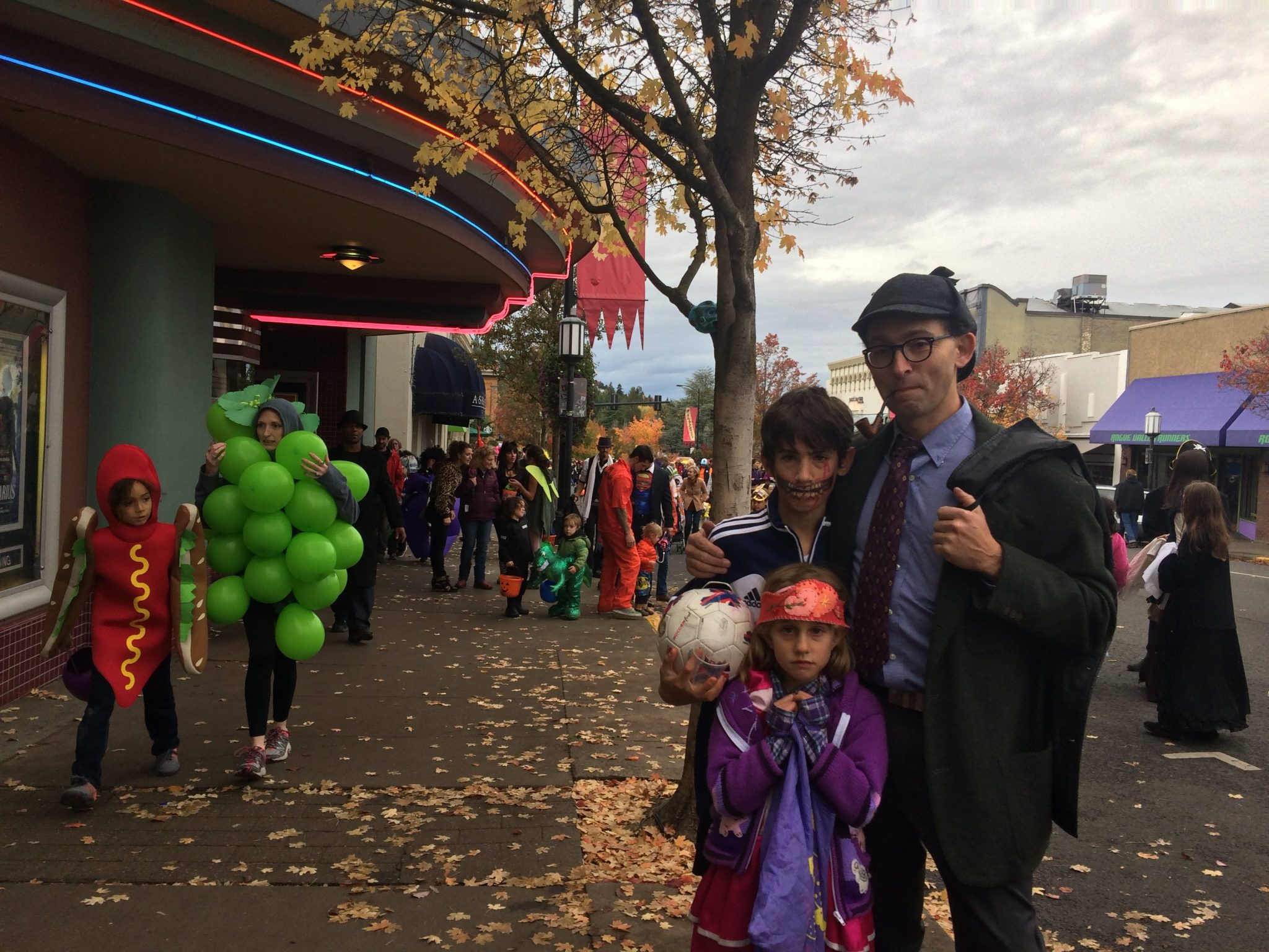 Mr. Sherlock Holmes accompanied by a zombie soccer player and a princess outside the Varsity Theater on Halloween in Ashland, Oregon
