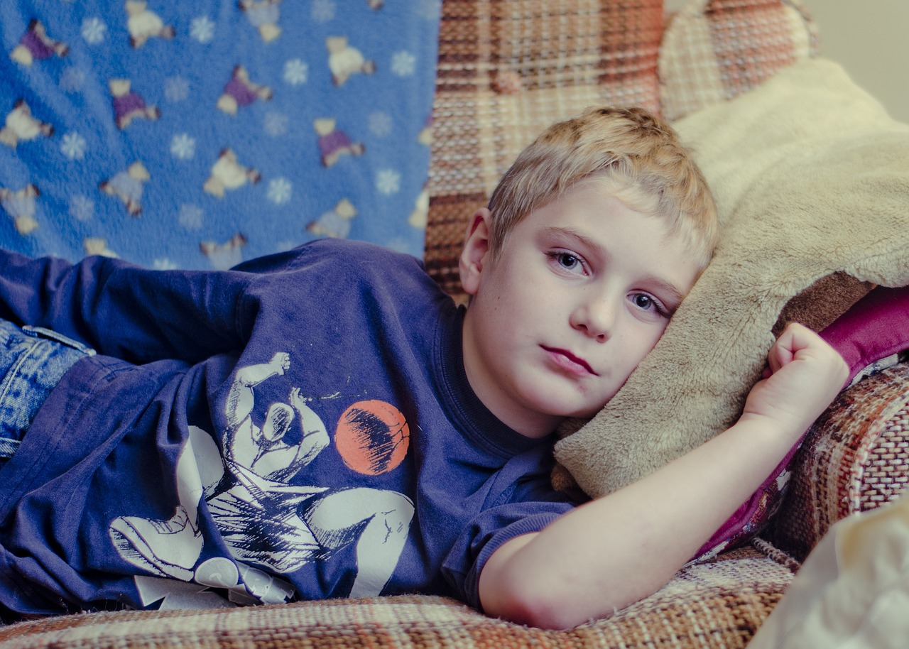 Sick child on couch. America's children are over-vaccinated and unhealthy | Jennifer Margulis