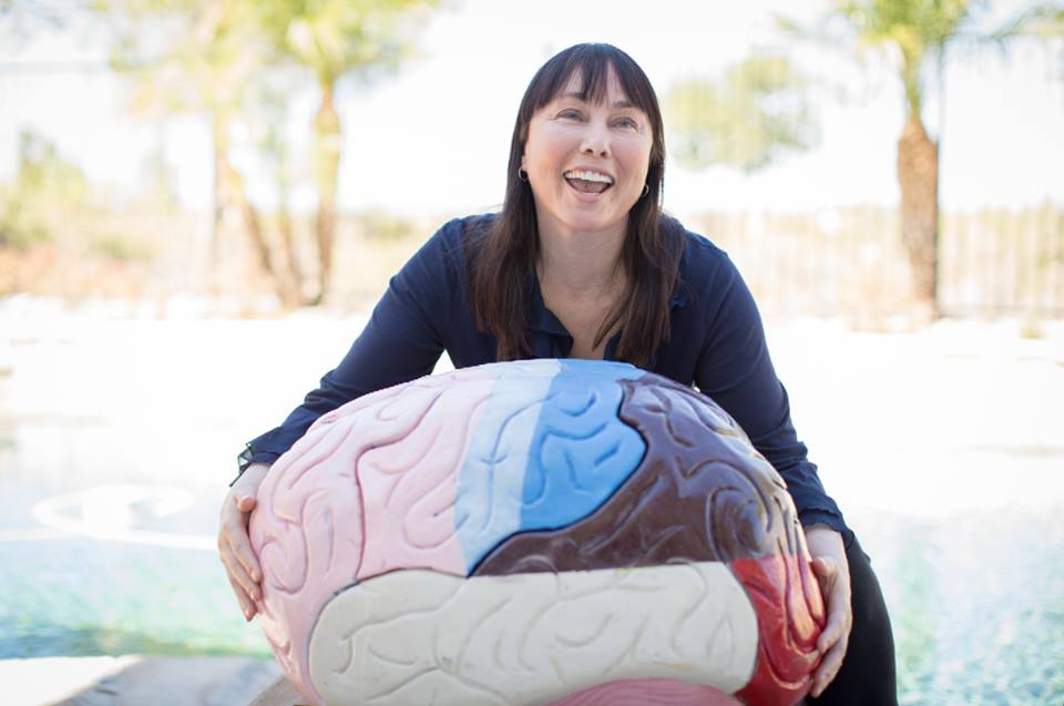 Mental health expert Lynette Louise raised eight children as a single mom. Photo of her holding a brain. Via JenniferMargulis.net