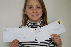 Holding up the donation envelopes before she mailed them. Instead of gifts, she asked friends to bring charitable contributions. We had an amazing green birthday party for her 8th birthday. | Jennifer Margulis