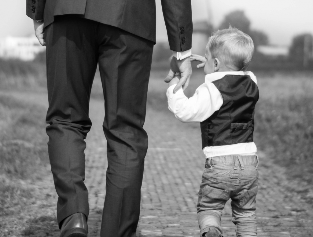 A dapper looking father wearing a suit holds his toddler's hand. It's almost Father's Day. Photo by Sabine van Straaten.