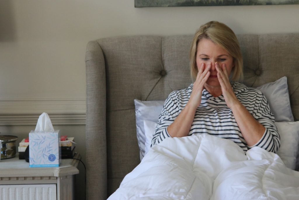 Treating a sinus infection without antibiotics, natural remedies that work. Photo of a sick woman in bed by Nicole Johnson. | Jennifer Margulis
