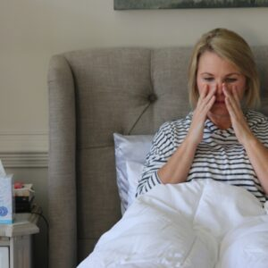 Treating a sinus infection without antibiotics, natural remedies that work. Photo of a sick woman in bed by Nicole Johnson.   Jennifer Margulis