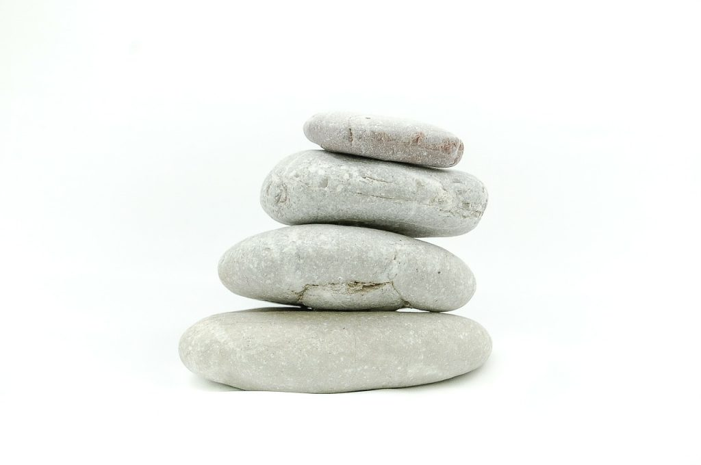 Excellent advice on how to meditate. Photo of four rocks piled up on a white background via Pixabay. | Jennifer Margulis
