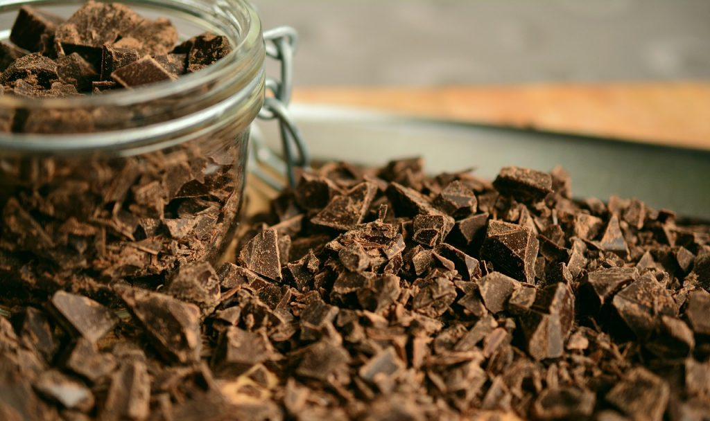 This is a recipe for healthy chocolate mocha cake that is sweetened with apples and dates. Photo of a jar of chocolate chunks spilling out. Via Pixabay. | Jennifer Margulis