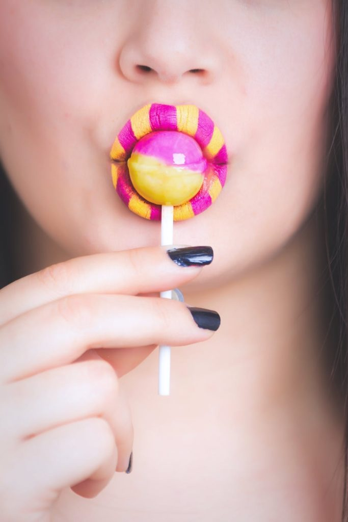 Sugar and Glyphosate: A Tale of Two Toxins. Photo of a woman with yellow and pink lipstick sucking a lolly. Courtesy of Oleg Magni via Pexels. | Jennifer Margulis