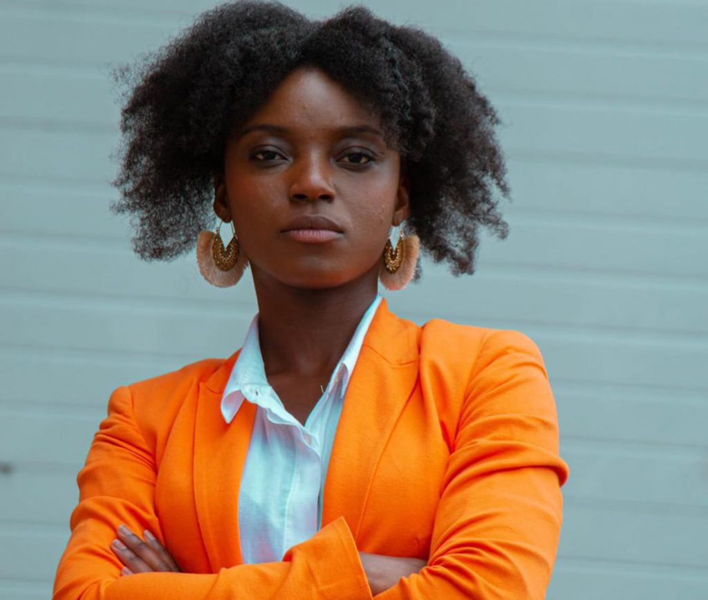 Scientific debate is needed during a pandemic. Photo of an African-American woman wearing an orange blazer via Unsplash. | Jennifer Margulis, Ph.D.