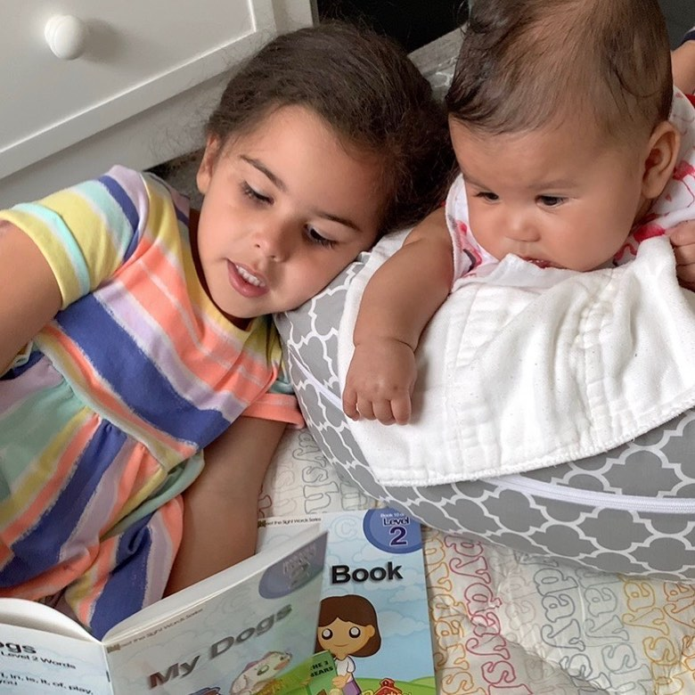 "Dr. Rachael Ross, M.D./Ph.D., opposed mandatory vaccination: ""These are my kids, not the government's. Photo of a child reading a book to a baby via Facebook. 