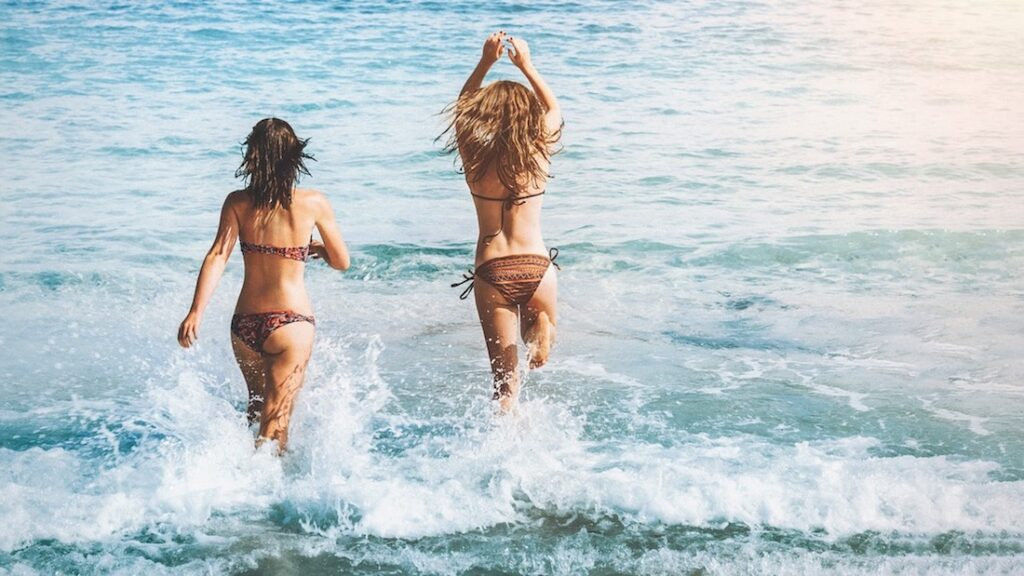Two women splash into the waves. The Case Against Lockdowns by Jennifer Margulis.